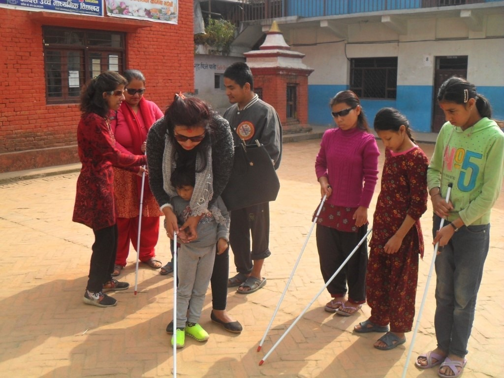 A trainer is teaching a visually impaired child how to use the white cane. Other participants are also seen in the photo.