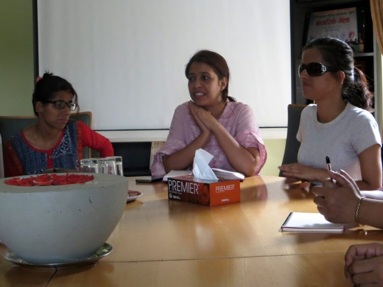 Two ladies are sitting side by side, and the one in the middle is speaking.