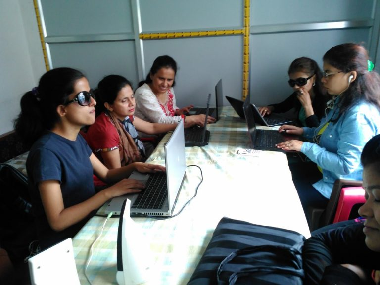 A group of ladies is seen using the laptop sitting around a table
