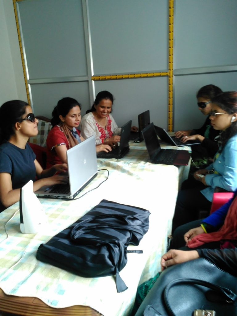 A group of women sitting around the table and using the laptop.