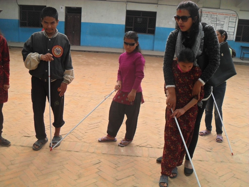 the trainer is guiding a little girl on how to use a white cane.