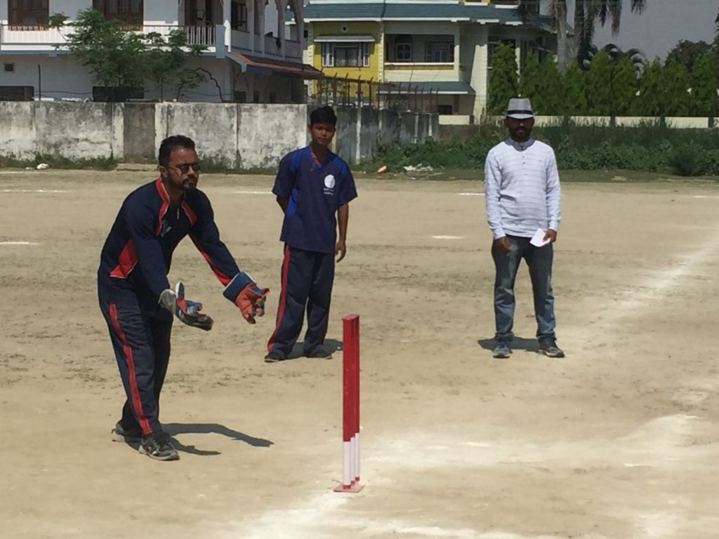 A person is trying to hit a ball with a cricket bat during the game.