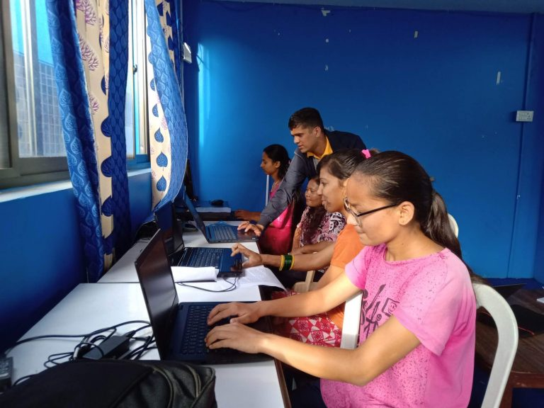 young women with disabilities practicing the computer skill taught by the trainer.