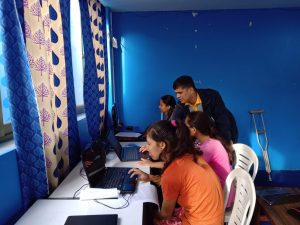 computer trainers teaching the young women with disabilities.